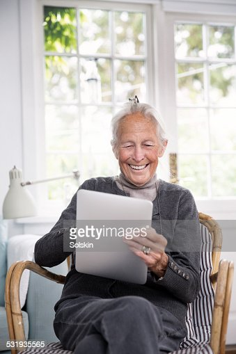 Elderly woman looking at tablet, smiling