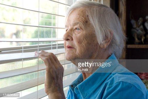 Elderly woman looking out a window.