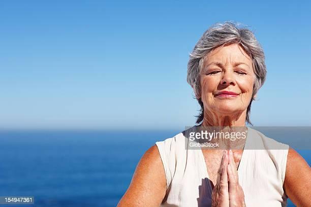 Femme pratiquant yoga avec vue sur l'océan en arrière-plan