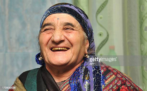 A elderly woman member of Yezidi community smiles at home in the Armenian village of Zovuny some15 km outside Yerevan on May 1 2013 The Yezidi are...