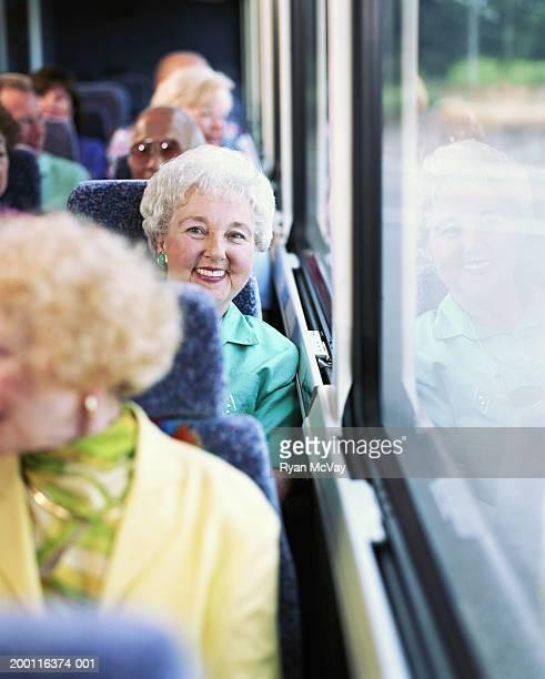 Elderly woman on coach bus, smiling, portrait