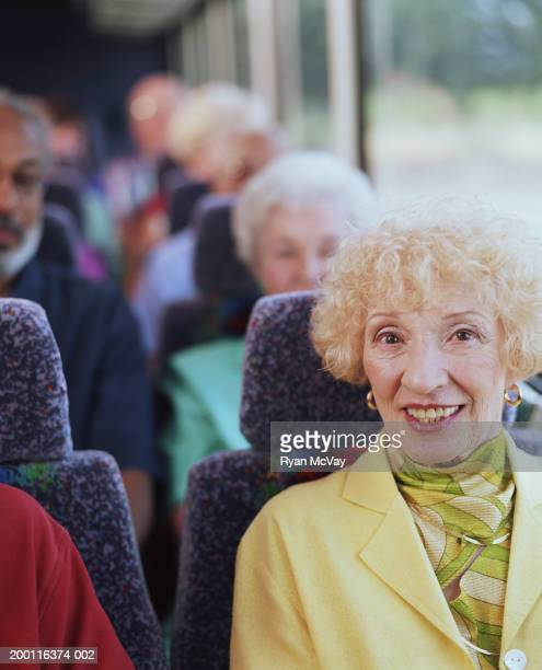 Elderly woman on coach bus, smiling, portrait