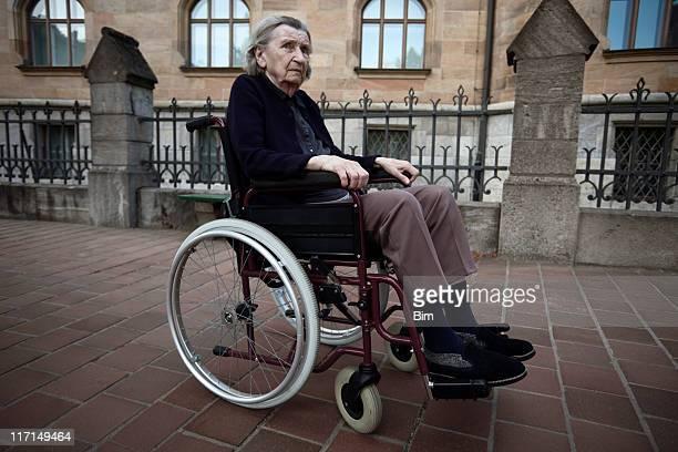 Ältere Frau im Rollstuhl vor einer alten Gebäude