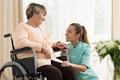 Elderly woman on wheelchair in nursing home with her care assistant