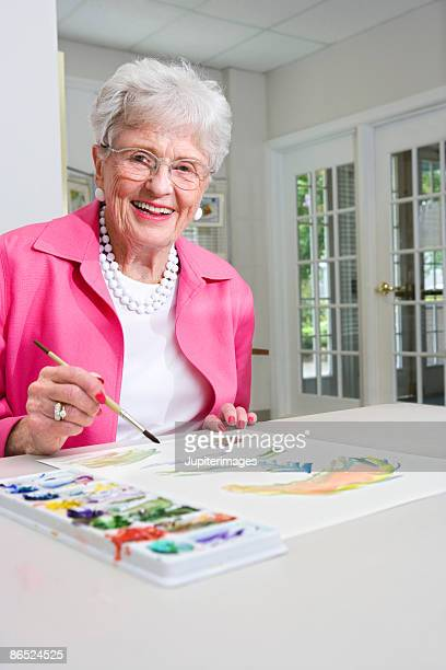 Elderly woman painting watercolors