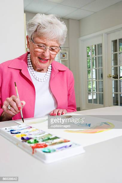 Elderly woman painting with watercolors