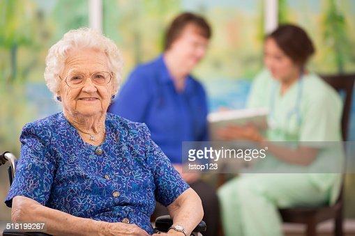 Elderly woman patient foreground. Nurse, daughter. Nursing home.