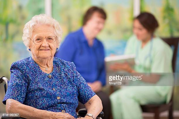 Elderly woman patient foreground. Nurse, daughter. Nursing home.
