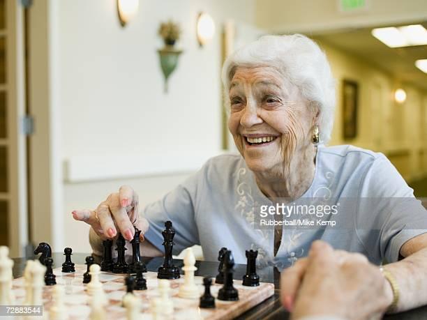 Elderly woman playing chess