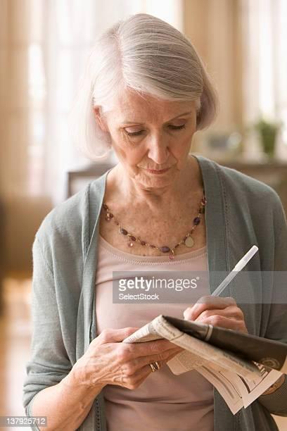 Elderly woman playing crosswords
