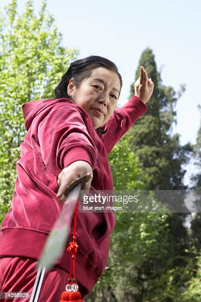 Elderly woman practices swordplay in a park.