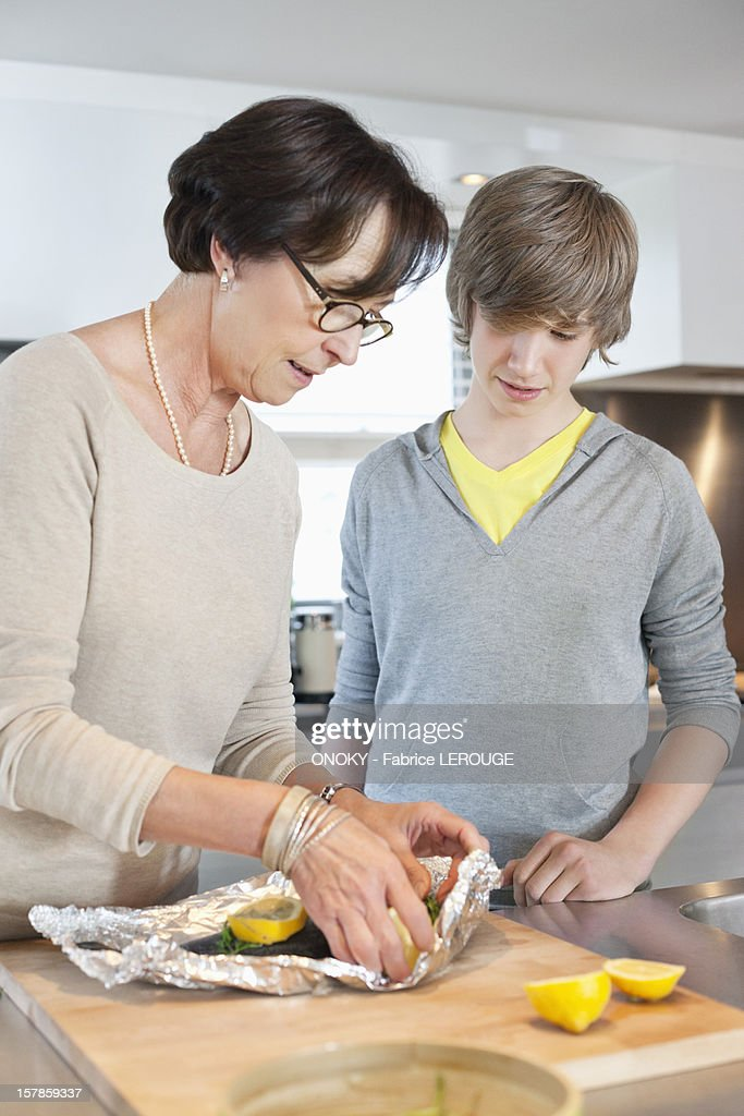 Elderly woman preparing seafood with her grandson in a kitchen : Stock Photo