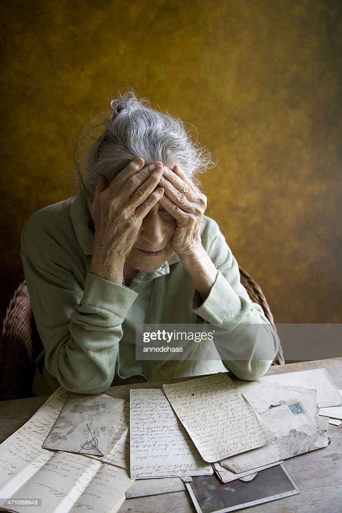 Elderly woman reminiscing over old letters and photos
