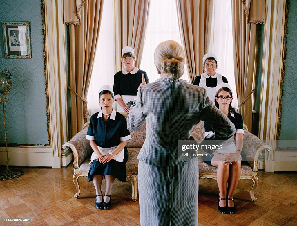 Elderly woman reprimanding domestic staff, rear view : Stock Photo