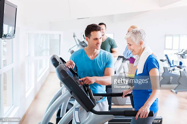 Elderly woman running on a treadmill at the gym