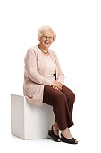 Elderly woman seated on a cube looking at the camera and smiling isolated on white background