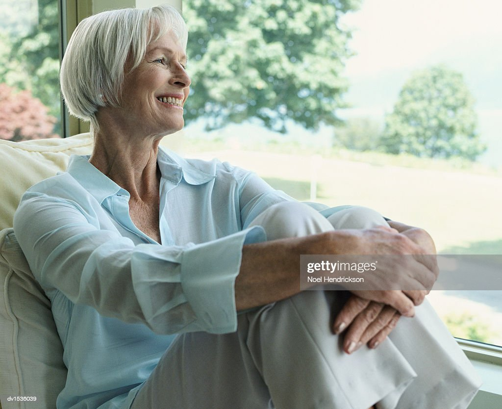 Elderly Woman Sitting at a Window Looking Out Into a Garden
