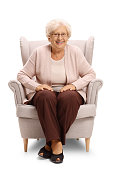 Elderly woman sitting in an armchair and smiling isolated on white background