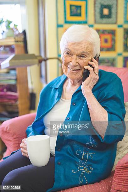 Elderly woman sitting tea and talking on a cell phone