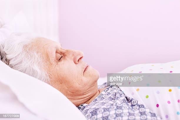 Elderly woman sleeping in her bed at home wearing pajamas