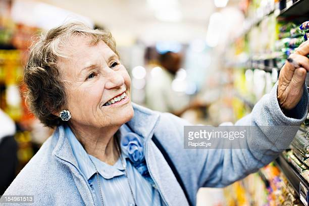 Elderly woman smiles as she chooses goods in supermarket