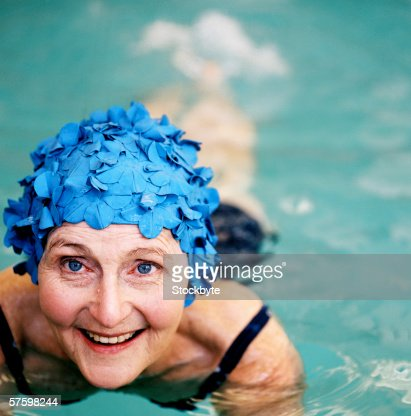 Elderly woman smiling wearing a swimming cap in a swimming pool