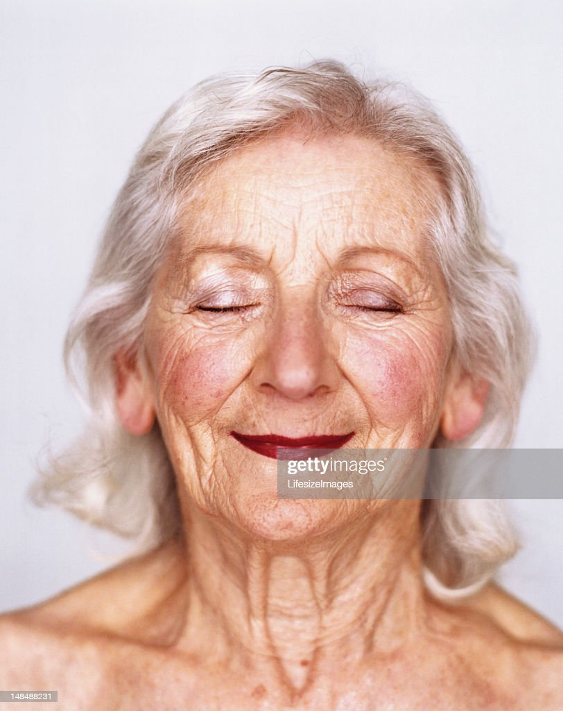Elderly woman smiling with eyes closed, portrait, close-up : Stock Photo