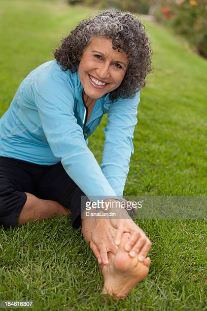 Elderly woman stretching outside