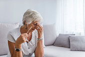 Elderly woman suffering from headache at home. Close up aged woman with headache. Health care, pain, stress, age and people concept