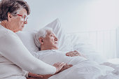 Elderly woman supporting sick husband lying in bed at hospital