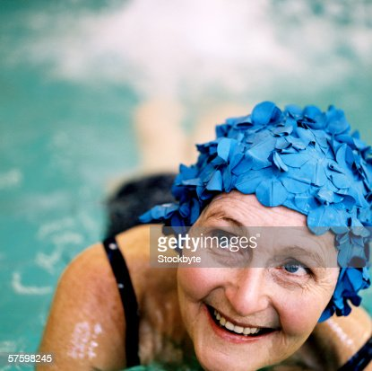 elderly woman swimming in swimming pool wearing a swimming cap