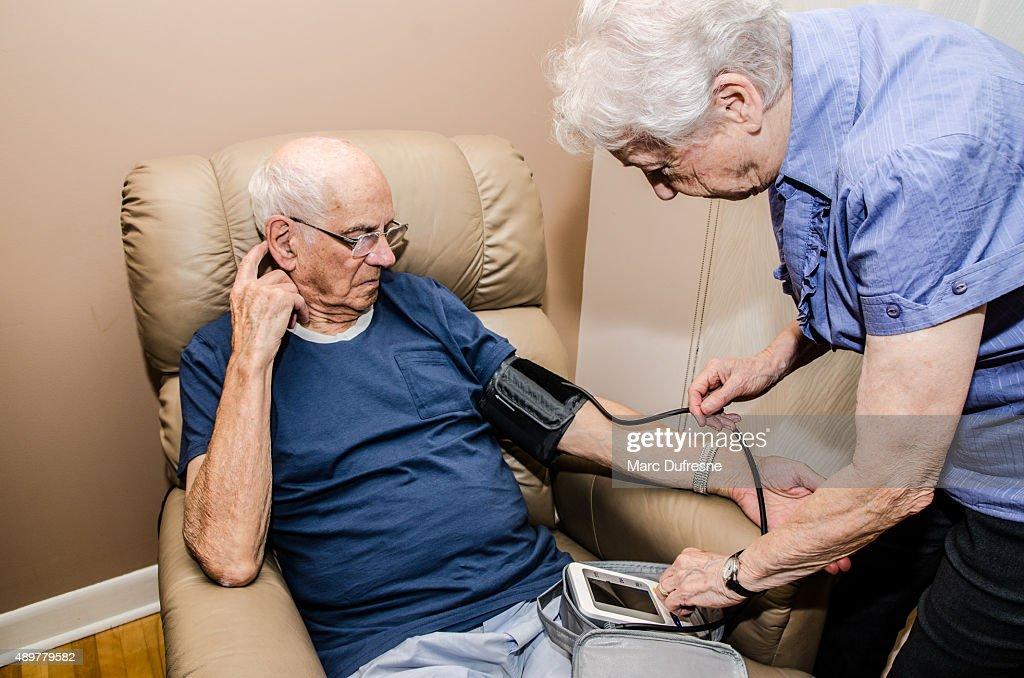 Elderly woman taking blood pressure of her husband