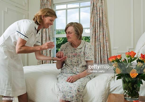 Elderly woman taking pill from nurse