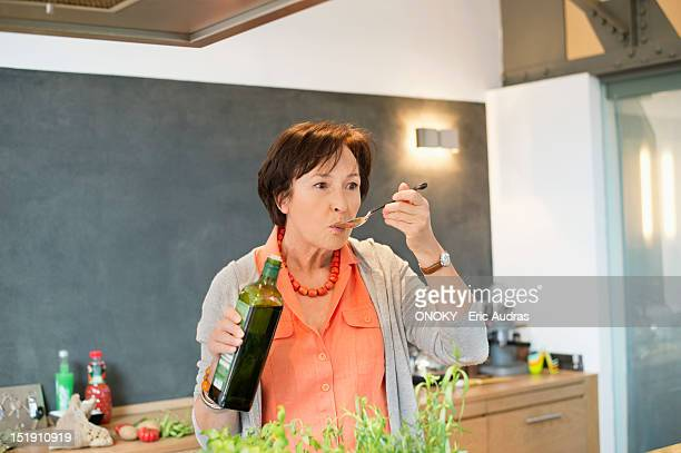 Elderly woman tasting olive oil in the kitchen