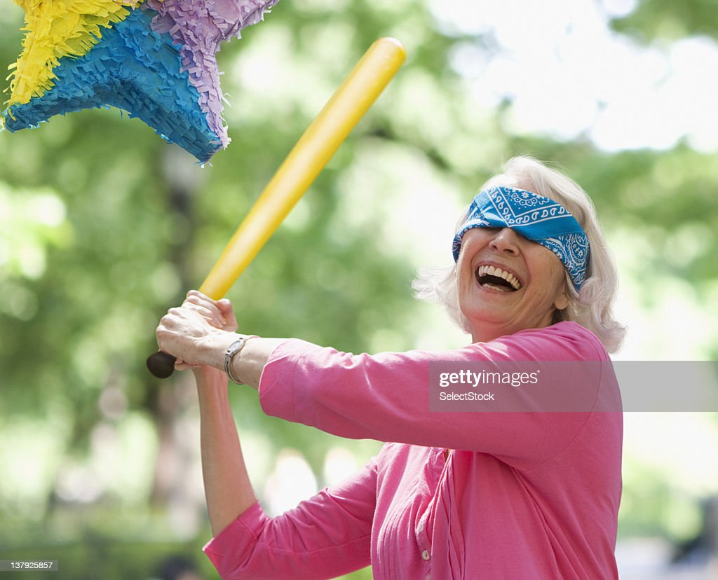 Elderly woman trying to hit a pinata : Stock Photo