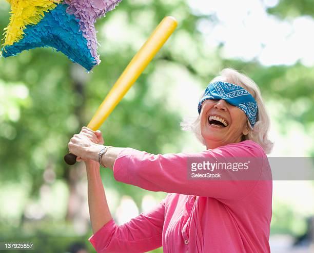 Ältere Frau versucht, auf eine Piñata