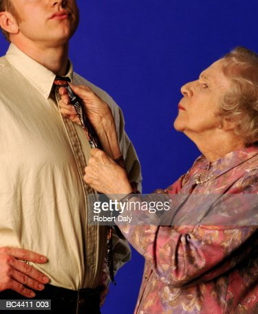 Elderly woman tying young man's tie, close-up