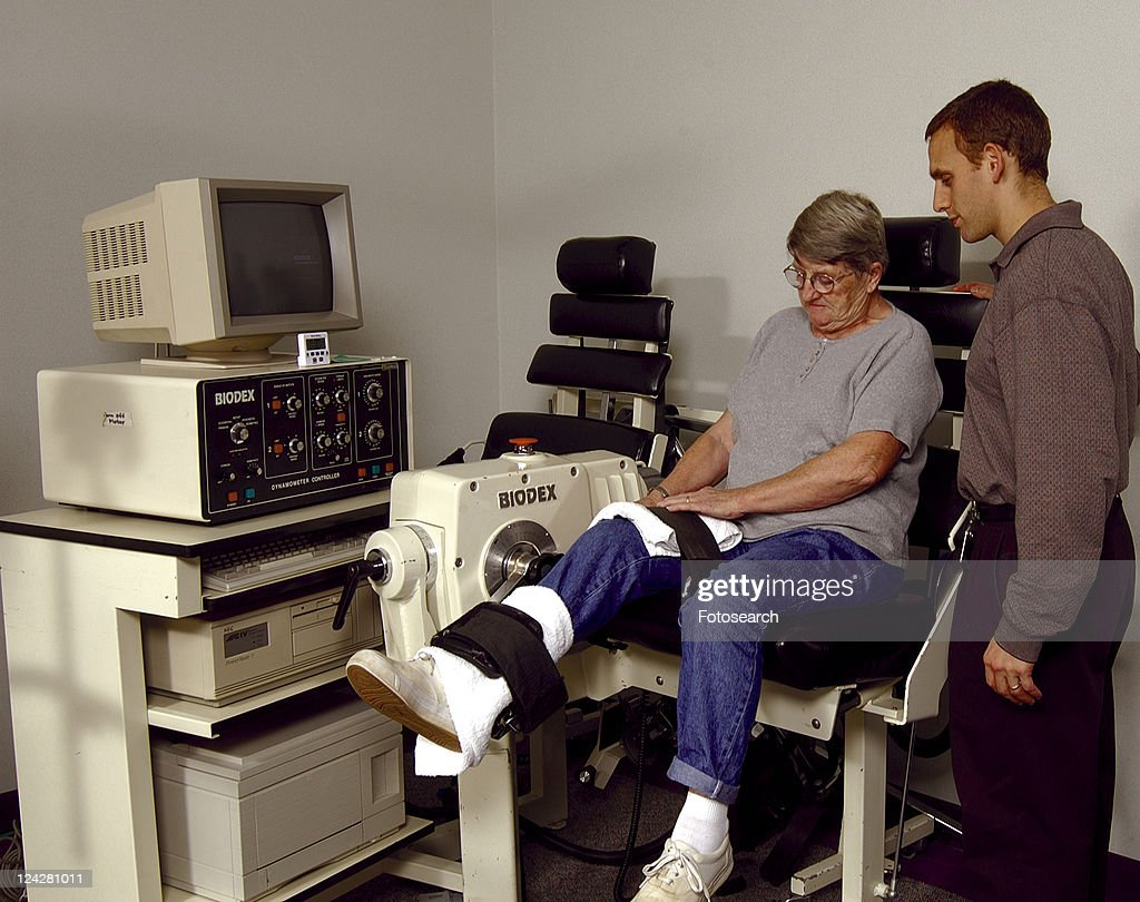 Elderly woman utilizing a physical therapy machine under the observation of her physical therapist. : Stock Photo