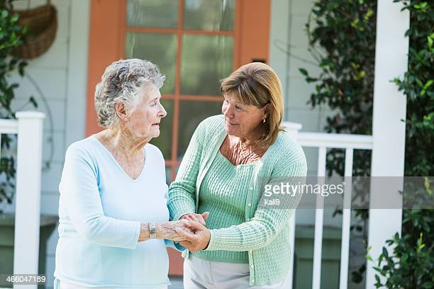Elderly woman walking with adult daughter