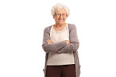 Elderly woman with her arms crossed looking at the camera and smiling isolated on white background