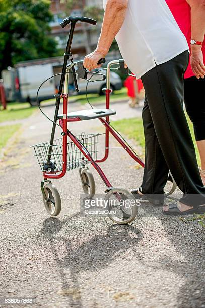 Elderly Woman with the walker and Caregiver