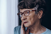 Close-up of elderly woman's face with glasses worried at home