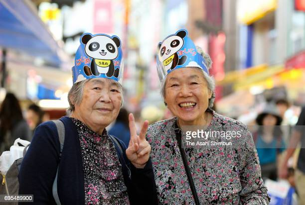 Elderly women celebrate wearing panda masks at Ameya Yokocho street as giant panda Shin Shin gave birth for the first time in five years at Ueno Zoo...