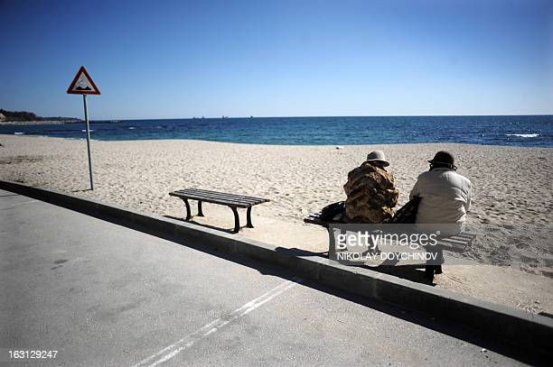 Elderly women chat on a bench at the beach in Bulgaria's main port on the Black Sea of Varna on March 5 the day after the death of a man who became a...