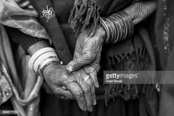 Elderly women holding another woman's hand.