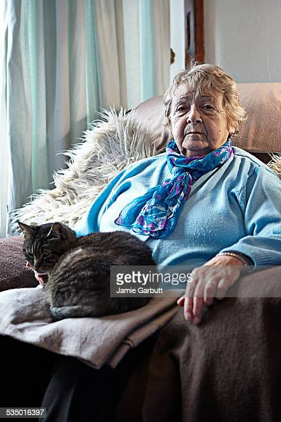 Elderly women sat with her cat at home.