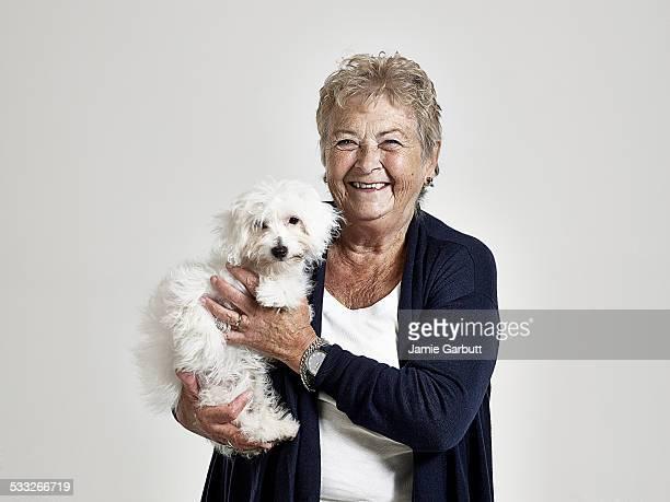 Elderly women smiling holding her puppy