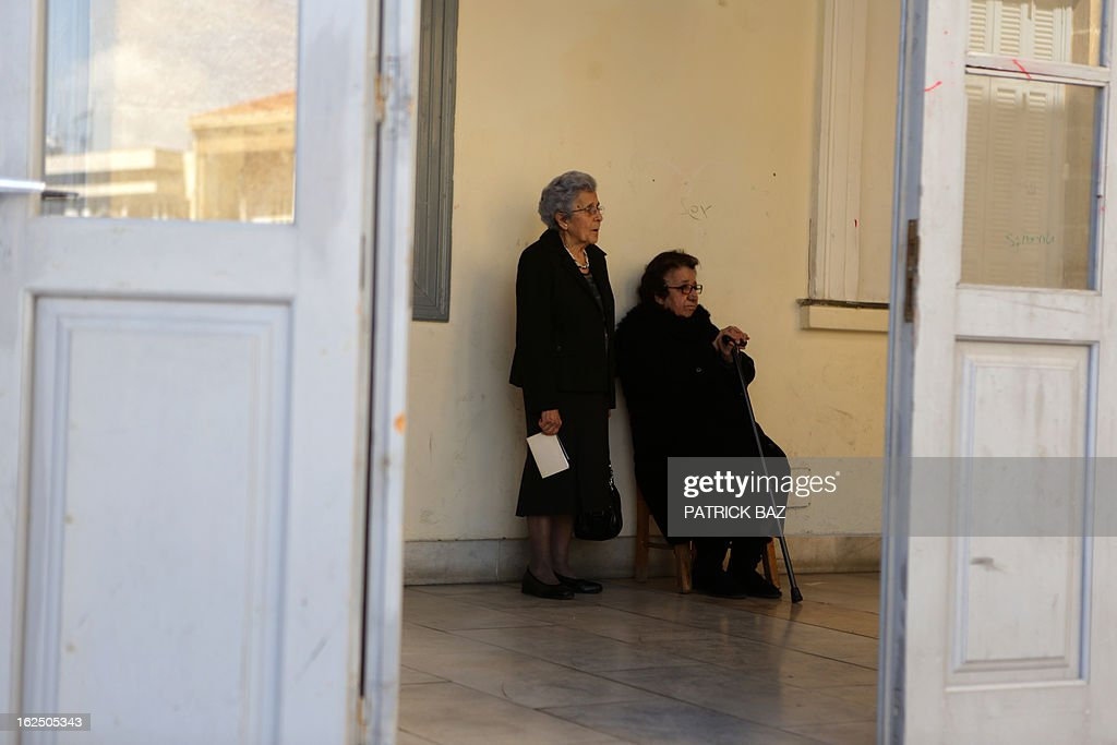 Elderly women wait outside of a polling station with their documents before voting in the second round of Cyprus' presidential on February 24, 2013 in the walled part of the Cypriot capital, Nicosia. Cypriots trickled in under bright, spring-like sunshine to vote in a left-right presidential runoff for electing a new leader to seal a crucial bailout for the EU state on the brink of bankruptcy. AFP PHOTO PATRICK BAZ