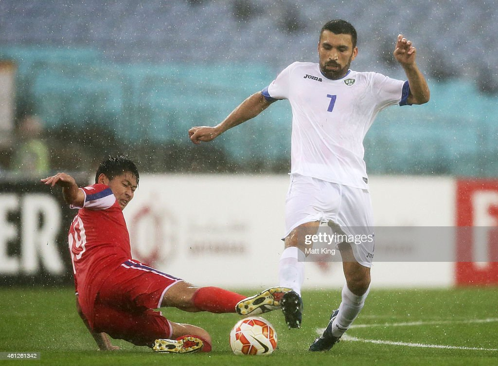 Eldorbek Suyunov of Uzbekistan is challenged by Ri Yong Jik of DPR Korea during the 2015 Asian Cup match between Uzbekistan and DPR Korea at ANZ...