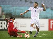 Eldorbek Suyunov of Uzbekistan is challenged by Ri Yong Jik of DPR Korea during the 2015 Asian Cup match between Uzbekistan and DPR Korea at ANZ...